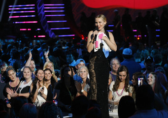 Show host Kristen Bell holds a paint-splattered towel as she speaks on stage during the 2014 CMT Music Awards in Nashville
