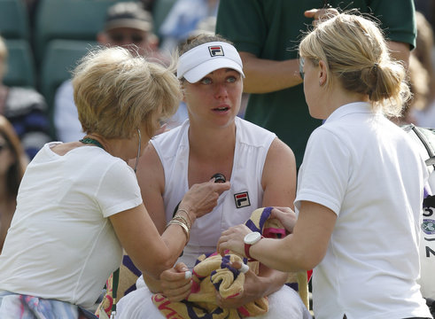 A doctor holds a stethescope to the chest of Vera Zvonareva of Russia during her women's singles tennis match against Kim Clijsters of Belgium at the Wimbledon tennis championships in London
