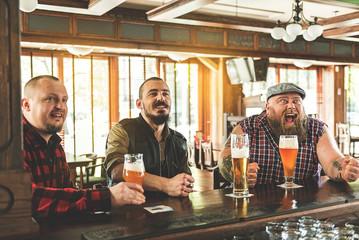 Joyful adult guys enjoying cold ale