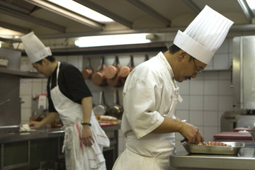 Cooks prepare dishes in the kitchen of the Prunier restaurant in Paris