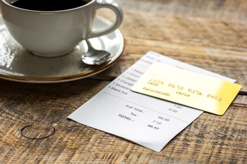 restaurant bill, card and coffee on wooden table background