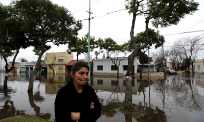 A woman stands outside her flooded home in Lujan