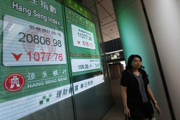 A woman walks past a panel displaying the Hang Seng Index, outside a bank in Hong Kong
