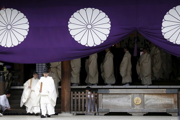 Shinto priests leave from the main shrine after a ritual to cleanse themselves during Annual Spring Festival at the Yasukuni Shrine in Tokyo