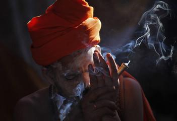 "A Sadhu smokes hashish during the ""Kumbh Mela"" in Haridwar"