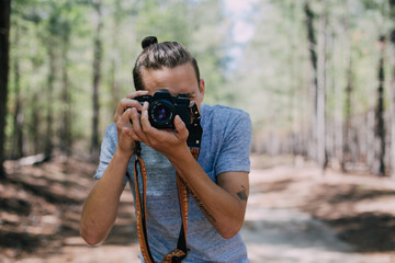 Young hipster millenial with man bun makes photograph on vintage analog film camera in middle of adventure trip through wild forest