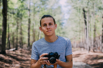 Handsome young man looks into the camera, softly smiling flirting ready to make a photo on analog vintage film camera in nostalgic forest