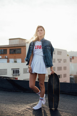 Vertical shot of pretty hipster millenial student who poses with her longboard on the industrial city environment, looks into camera with model expression