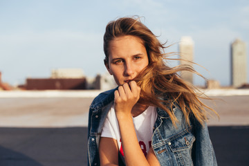 Portrait of a feminine young lady in trendy tshirt and denim jacket modelling on the rooftop of building on a windy sunset day