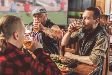 Three bearded guys enjoying beer in pub