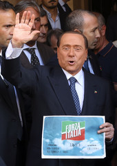 Berlusconi waves to supporters as he shows the logo of his re-launched political party Forza Italia in downtown Rome