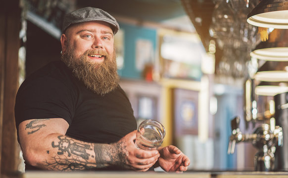 Cheerful tattooed bartender standing with smile