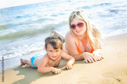 878936c4b8 Portrait of beautiful young parents and cute little girl in swimsuits and  sun glasses smiling,