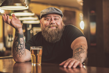 Obraz Smiling bearded male drinking beer in pub - fototapety do salonu