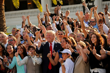 Trump leads his employees in a thumbs-up group photo after a campaign event with them at his Trump National Doral golf club in Miami, Florida