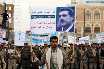 A follower of the Houthi movement holds up a banner depicting journalist Abdul Kareem al-Khaiwani during a demonstration commemorating an attack on pro-democracy protesters in Sanaa
