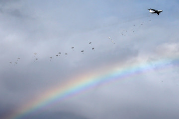 """Russian paratroopers jump past rainbow from an IL-76 transport plane during a joint Serbian-Russian military training exercise """"Slavic Brotherhood"""" in the town of Kovin"""