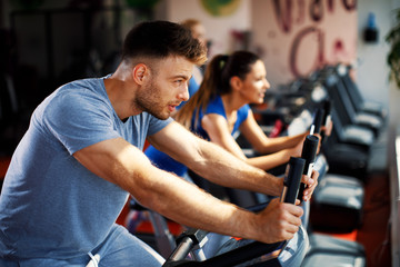 Young man and woman warming up on bikes in the gym
