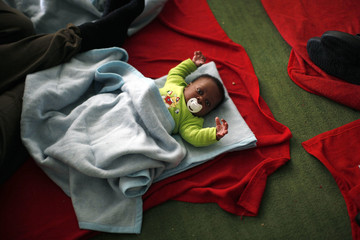 An African child immigrant lies inside a sports center after arriving on a rescue ship at the southern Spanish port of Tarifa