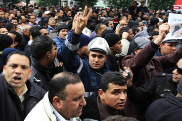 A policeman flashes a peace sign during a protest in Tunis