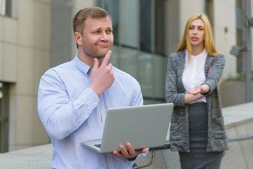 Clever businessman with laptop ahead of business lady who talking to him outdoor