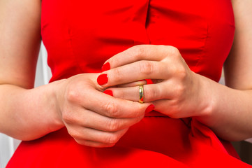Woman is taking off her wedding ring - divorce concept