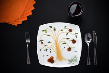 Composizione con elementi del tipo pasta, piatto, posate, tovaglioli  e bicchiere posizionati artisticamente su tavolo nero. Sfondo con spazi liberi per testo.