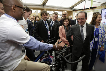 French President Francois Hollande looks at a man who cycles to produce electricty at a stand in the Climate Generations area during the World Climate Change Conference 2015 (COP21) at Le Bourget