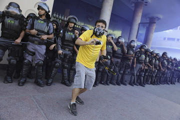 A demonstrator wearing a Brazil jersey films with his cameras in front of riot police during clashes before the World Cup final match between Argentina and Germany in Rio de Janeiro