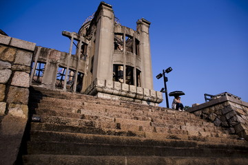 A woman sits in front of Atomic Bomb Dome in Hiroshima