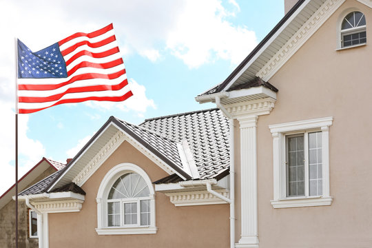 Waving USA flag and house on background