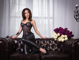 Sexy brunette in corset and leather pants. Sensual young woman on a leather sofa.