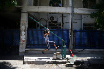 A boy pulls a lever as he fills water containers, in the rebel held besieged town of Douma, eastern Damascus suburb of Ghouta