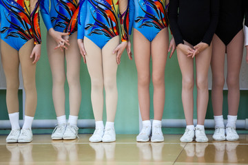 Children feet of young athletes in white sports sneakers and color costumes stand in line in the gym