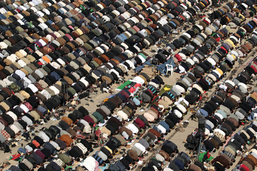 Protesters attend Friday prayers next to coffins containing bodies of rebels killed in Bin Jawad during clashes with forces loyal to Libyan leader Gaddafi, in Benghazi