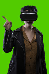 Woman isolated on a green background or greenscreen wearing a VR virtual reality headset.  The image depicts technology and can be used for composites.