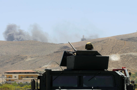 Lebanese army soldier sits atop army vehicle at the entrance of the Sunni Muslim border town of Arsal, in eastern Bekaa Valley, as smoke rises during clashes between Lebanese army soldiers and Islamist militants