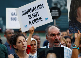 Demonstrators shout slogans during a protest against the arrest of three prominent activists for press freedom, in central Istanbul