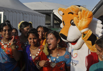 Indian artistes pose for a picture with the mascot of Commonwealth Games at the athletes village in New Delhi
