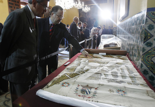 People look at a recovered cartographic map from the 18th century displayed at the Foreign Ministry in Lima