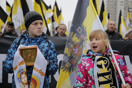 """Children hold icon and historic flag of Russian empire as they attend """"Russian March"""" demonstration on National Unity Day in Moscow"""