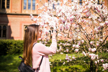 Happy woman traveler take photos by camera with cherry blossoms tree on vacation while spring