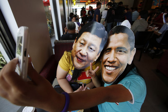 "Members of activist Party List group ""Akbayan"" wearing picture cut-out masks of U.S. President Barack Obama and China's President Xi Jinping make a ""selfie"" with a mobile phone in a coffee shop in Quezon city"