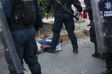 Federal police officers surround an injured man during clashes in Chilpancingo, Guerrero