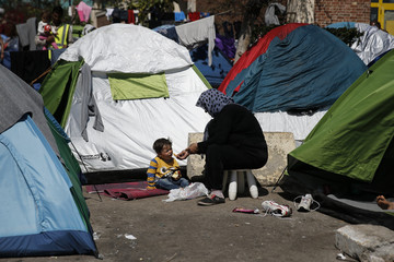 A migrant gives a fruit to a child next to their tent at a makeshift camp for refugees and migrants at the port of Piraeus, near Athens