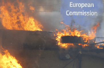 A logo on the European Commission building is seen behind a burning caravan during clashes outside an European Union farm ministers emergency meeting at the EU Council headquarters in Brussels