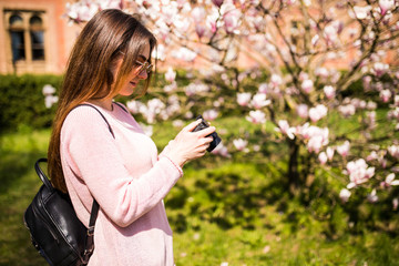 women traveler use camera take a photo magnolia blossoms