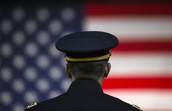 A U.S. Army officer listens to a speaker with the U.S. flag in the background at the Hiring our Heroes job fair in New York