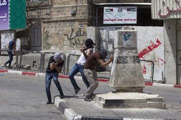Palestinian stones throwers take cover during clashes with Israeli soldiers in Hebron