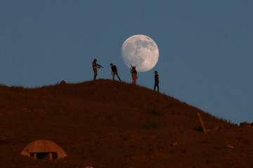 Free Syrian army fighters stand atop of a hill as the moon is seen in the background in the south of Nawa city, in Deraa Governorate